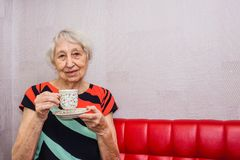 Back coffee. Happy vigorous mature woman laughing while sitting and drinking coffee royalty free stock image