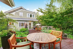 Back deck of guest house with wooden table set. Luxury house exterior. Northwest, USA Stock Photo