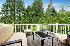 Back deck with outdoor furniture and nice view. Comfortable beige sofa, ottoman and black coffee table. Northwest, USA Stock Photography