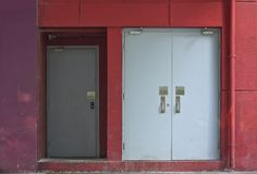 Back Door or Back Entrance. Back doors within a red painted concrete wall of an industrial building. Sidewalk of an industrial building Stock Image