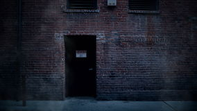 Back door entrance to old brick building in alley with steam rising. stock video footage