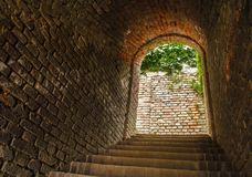 Back drop brick wall, stairs and entrance with bright light and tree at the end on the way up to clock tower on hill in Graz Royalty Free Stock Photos