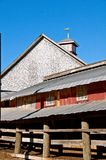 Cupola with a wind vane of a trotting horse. The back end of a ranch stable barn displays a cupola with a weather vane of a horse trotting stock photo