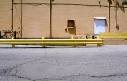 Back Entrance. The back of a business with door, guard railing and cables Royalty Free Stock Photography
