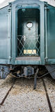Back entry to antique pullman train, landing and door. Pullman train on tracks.  Green door with circle window on landing platform with protective fence Royalty Free Stock Photo