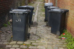 Back-entry and Wheelie Bins 02. Black domestic waste-bins in a back-entry between two rows of terraced houses Royalty Free Stock Photo