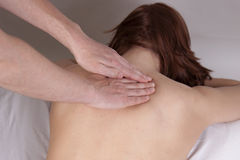 Back examine. Young woman lies on table while massage therapist examines her shoulders, back stock photos