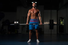 Back Exercise With Barbell In Fitness Center. Latin Bodybuilder Doing Heavy Weight Exercise For Back With Barbell In Modern Gym Stock Photography
