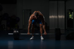 Back Exercise With Barbell In Fitness Center. Muscular Hispanic Man Doing Heavy Weight Exercise For Back With Barbell In Modern Gym Royalty Free Stock Photography