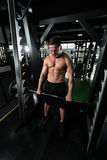 Back Exercise With Barbell In Fitness Center. Muscular Man Doing Heavy Weight Exercise For Back With Barbell In Modern Gym Stock Photo