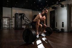 Back Exercise With Barbell In Fitness Center Stock Image