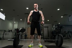 Back Exercise With Barbell In Fitness Center. Young Bodybuilder Doing Heavy Weight Exercise For Back With Barbell In Modern Gym Royalty Free Stock Photo