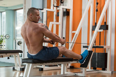 Back Exercise. Muscular Young Man Doing Heavy Weight Exercise For Back Royalty Free Stock Image