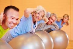 Back exercises in fitness center. Elderly group doing back exercises in a fitness center Stock Images