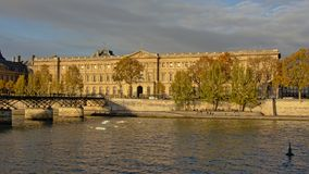 Back facade of Louvre museum, Paris. Back facade of Louvre museum and Pont des Arts bridge on a sunny day in Paris, France Royalty Free Stock Photos