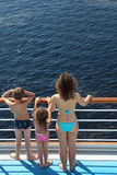Back of family standing on deck of ship. Back of mother, son and daughter dressed in swimsuits standing on deck of ship and looking at water Royalty Free Stock Photography