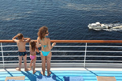 Back of family standing on deck of ship. Back of mother, son and daughter dressed in swimsuits standing on deck of ship and looking at cutter Royalty Free Stock Photos