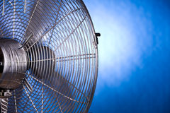 Back of fan. Backside of a working metal fan on a blue background Royalty Free Stock Photography