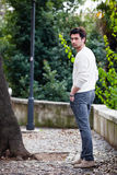 Back fashion young man standing and posing. Street in a old park Royalty Free Stock Images