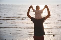 Back father dad and baby boy son lifestyle sitting on shoulders. At sea beach, sunset stock photography