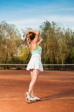 Back of female tennis player serving Royalty Free Stock Photos