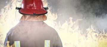 Composite image of back of firefighter. Back of Firefighter against grey room Royalty Free Stock Image