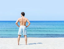 Back of a fit young man on the beach Royalty Free Stock Images