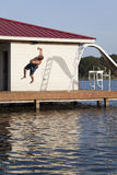 Back Flipper. A man is doing a back flip off the end of a dock into the water Stock Photography