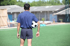 Back of a football referee holding the ball Royalty Free Stock Image