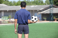 Back of a football referee holding the ball Stock Images