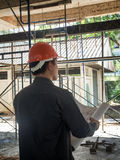 Back of foreman with blueprint. On construction site stock photos