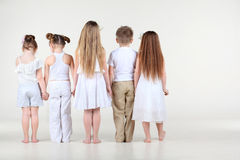 Back of four little girls and boy standing and holding hands. Back of four cute little girls and one boy in white clothes standing and holding hands Stock Images