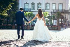 Back full-length portrait of the stylishly dressed newlywed couple holding hands in the beautiful town street. Back full-length portrait of the stylishly Stock Images
