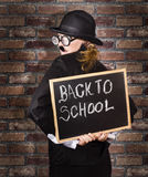 Back to school teacher holding blackboard and chalk. Back of a funny looking headmaster holding black board with back to school written in chalk. School brick Royalty Free Stock Photos
