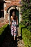 Girl back antique wall door, Groot Begijnhof, Leuven, Belgium royalty free stock photo