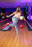 Back of girl making throw of ball in bowling club. Back of girl wearing jeans and white T-shirt making throw of ball in bowling club stock image