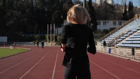 Back girl running at the stadium. Runner training at the stadium stock footage