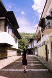 Back of a Girl Walking through the antique streets of a traditional village of Bulgaria in a blue dress stock photos