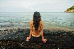 Back girl in yellow bikini on stony shore blue sea. girl in yellow bikini. Back view girl in yellow bikini. tanned girl in sits on sea rock. Female in bathing royalty free stock image