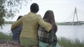 Grandmother who sitting with two granddaughters in the banch and looking at beautiful river in the forest. Lady hug her. Back of grandmother who sitting with two stock footage