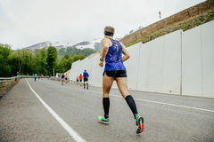Back group of runners athletes running road mountain marathon. Rosa Khutor, Russia - May 7, 2017: back group of runners athletes running road mountain marathon Stock Image