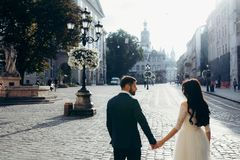 Back half-length view of the gorgeous happy newlywed couple holding hands in the sunny town street. Back half-length view of the gorgeous happy newlywed couple Stock Photography