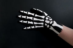 Back of hand painted to look like bones for halloween. A person`s hand painted black and white to look like a skeleton hand of bones stock photo