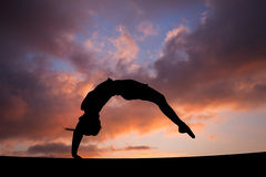Back handspring of female gymnast in sunset sky. Back handspring of silhouetted female gymnast in sunset sky Royalty Free Stock Photography