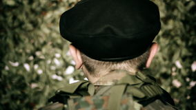 Back of the head of a soldier in front of camouflage net Stock Photos