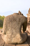 Back of Headless Statue at Borobudur Temple with mountain range in the background Stock Photo