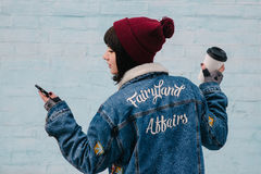 Back hipster young girl is holding a coffee and looking at phone. Back hipster young girl in a blue denim jacket, which is holding a coffee and looking at phone Royalty Free Stock Photo