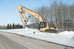 Back hoe digging snow on the side of a highway Stock Photo
