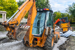 Back hoe heavy machinery. Pair of heavy machinery on construction site Stock Image