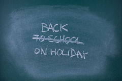 Back on holiday. Concept. Writing back to school scored out and replaced with text , school chalkboard (blackboard Stock Image